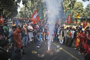 BJP supporters burn firecrackers to celebrate the party