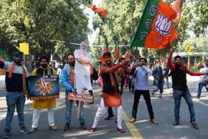 BJP supporters celebrate outside the party headquarters in New Delhi after early counting of votes indicated a comfortable win in Gujarat and Himachal Pradesh.