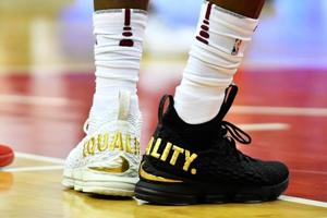In show of equality, LeBron James wears 1 black shoe, 1 white shoe in...