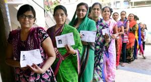 Women wait to cast their vote during repolling at a booth in Daskroi constituency, at Ahmedabad.