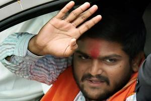 Patidar community leader Hardik Patel waves at supporters during a road show for the second phase of Gujarat assembly elections, in Ahmedabad.