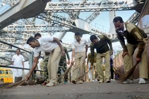 CRPF jawans wield broom at Rabindra Setu during a Swachh Bharat Abhiyan programme in Kolkata.