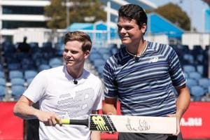 Australia cricket team skipper Steve Smith (L) presents Canadian tennis pro Milos Raonic with a signed bat during a promotional event at Melbourne Park on Thursday.