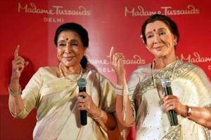 Singer Asha Bhosle poses with her wax statue during its unveiling at Madame Tussauds in New Delhi.