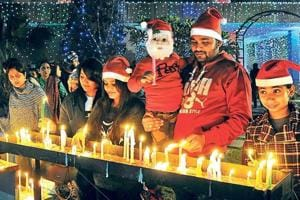 People light candles and offer prayers on the eve of Christmas at the Sacred Heart Cathedral in New Delhi, on Sunday