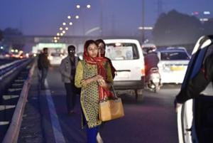 A woman waits for a cab on the Delhi-Gurgaon Expressway.