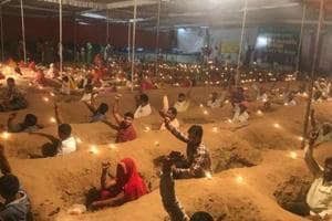 Farmers near Jaipur protest by sitting in pits amid Diwali lamps.