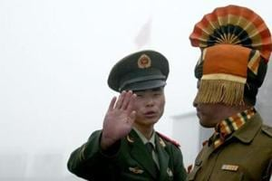 This file photo shows a Chinese soldier gesturing next to an Indian soldier at the Nathu La border crossing between India and China in Sikkim.