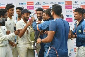 Vidarbha captain Faiz Fazal and his teammates celebrate with the Ranji Trophy after beating Delhi in Indore on Monday.