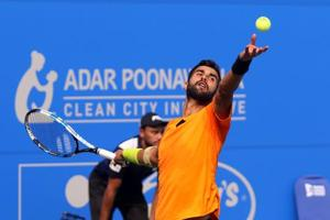 Yuki Bhambri serves to Pierre-Hugues Herbert during their second round at the TataOpen tennis tournament (Maharashtra) at the Shiv Chhatrapati Sports Complex in Pune on Wednesday.