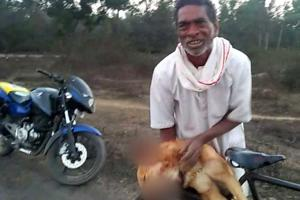 Forty-eight-year-old Sai cries as he carries the body of the dog.