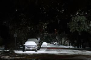 Snow covers cars along a street as snow and cold weather blanket Savannah, Georgia, on Thursday.