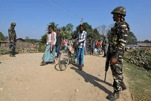 Villagers walk past Central Reserve Police Force (CRPF) personnel patrolling a road ahead of the publication of the first draft of the National Register of Citizens (NRC) in the Juria village of Nagaon district in Assam on December 28, 2017.
