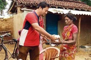 Mangesh Jha hands over sanitary napkins to a woman at Jonha village in Ranchi.