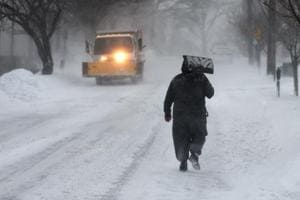 A man carries a shovel up the middle of the street in Greenwich, Connecticut on January 4, 2018.