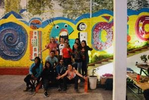Some of the creative artists who participated in the Roadtrip Experience Project in November, with a mural they painted in collaboration with each other and local artists.
