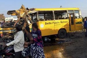 Passers-by look at the school bus that was wrecked due to an accident, in Indore on Friday.