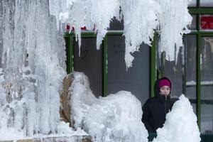 A woman passes an ice-covered fountain in New York