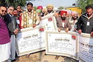 Farmers displaying their cheques received under the crop loan-waiver scheme in Mansa on Sunday.