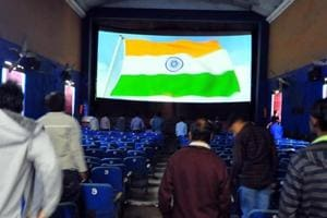 The audience stands for the national anthem at a theatre in Delhi.