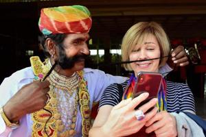 A foreign tourist clicks a selfie with a Rajasthani artiste with long moustache in Rajasthan's Bikaner.