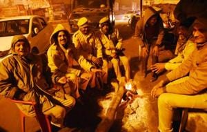Security personnel sit around a bonfire near KGMU crossing in Lucknow.