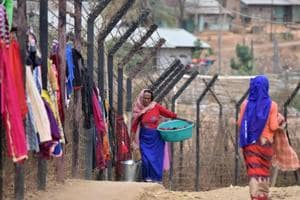 A woman carries her laundry past washing hanging up to dry on the India-Myanmar border fencing at Moreh, some 120 kms from Manipur capital Imphal.