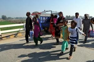 Border villagers move with their belongings to a safer place during shelling from the Pakistani side of the border at Arnia sector, in Jammu, on January 19.