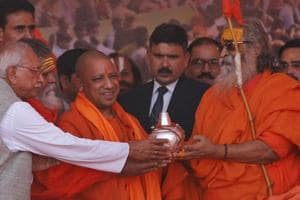 Hindu spiritual leader Jyotir Pitha Shankaracharya Vasudevanand Saraswati, right, presents a pot filled with holy water to Uttar Pradesh chief minister Yogi Adityanath at a meeting organised by the Vishwa Hindu Parishad during the annual Magh Mela fair in Allahabad on Friday.