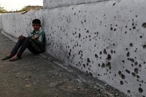 A boy shows splinters of mortar shell fired from the Pakistani side, in Arnia district of Jammu and Kashmir, on Thursday.