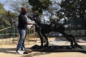 An artist works on a sculpture 'A Dog' at Millennium Park.