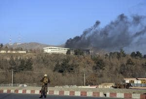 An Afghan security official stands guard as black smoke rises from the Intercontinental Hotel in Kabul on January 21, 2018.