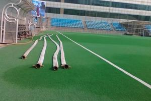 The temporary arrangement at Shivaji Stadium to sprinkle water on the hockey Astroturf, using fire brigade  hoses.