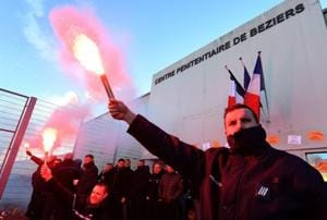 French prison guards clash with riot police, burn tyres during...