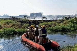 Firefighters inspecting the Bellandur lake in Bengaluru on Saturday. The lake, known for its high levels of pollution, caught fire on recently, sending out huge clouds of smoke on the Yemlur side.
