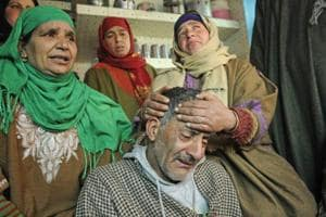 Javid Ahmed Lone, the father of class 12 student Suhail who was killed when the army opened fire against the protesters on Saturday in Ganawpora village of Shopian district, with his grieving relatives in Srinagar on Monday.
