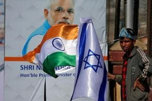 A man holds flags of India and Israel before installing them on a lamp post ahead of the visit of Israeli Prime Minister Benjamin Netanyahu in Ahmedabad on January 15, 2018.