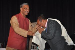Chief minister Trivendra Singh Rawat felicitates a teacher at a workshop on child protection in Dehradun.