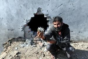 A villager shows a mortar shell near damaged wall of his house fired by Pakistan of the border at Arnia sector in Jammu on January 19. In just this year, at least 19 soldiers have been killed on both sides during ceasefire violations.