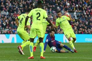 Barcelona's Lionel Messi in action with Getafe's Faycal Fajr in a La Liga contest at Camp Nou in Barcelona on Sunday.
