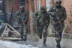 Army personnel take position during an encounter with militants, who were taking shelter in a building near a CRPF camp at Karan Nagar, in Srinagar, on Monday.