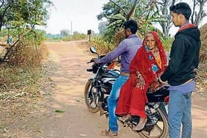 Septuagenarian Deventi Devi goes to the bank on a motorcycle to withdraw food subsidy in Ranchi.