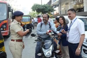 A motorist poses with the rose he was given by the Kalyan RTO officials on Wednesday.
