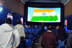 People stand for the national anthem before the start of a movie at a theatre in Indore.