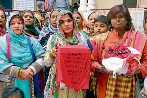 Pilgrims Shamiya (C) and Mala (R) from Karachi, Pakistan, holding ashes of their relatives at the Durgiana Temple serai in Amritsar on Thursday.
