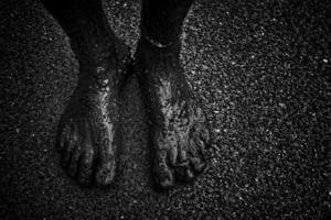 A sanitation worker's feet covered with muck.