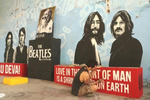A Canadian artist, who is a Beatles fan, gives final touches to a wall painting of the music legends.
