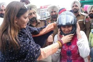 Veenu Badal, wife of local MLA and finance minister Manpreet Singh Badal, helping a woman wear a helmet at the launch of a traffic safety programme by the police in Bathinda on Friday.
