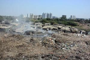 Schoolchildren walk past an illegal garbage dump yard at Wagholi. Residents say chronic garbage burning is leading to pollution of air and water.