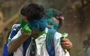 Students smear one another with colours ahead of Holi.
